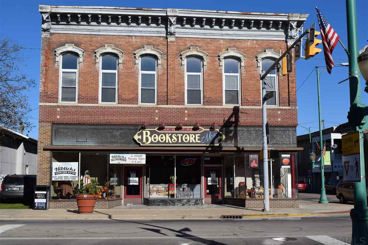 "Own your business and live in it too!  This unique historical downtown business has much to offer.  The Next Page Bookstore business comes with the property lock stock and barrel.  The Niblick\'s Bistro is a rented space, but the kitchen equipment stays with the property.  There is a conference room on the main floor to rent to groups.  There is another undeveloped space with street front as well!.  The upstairs flat is a 3 bedroom, 3 bathroom remodeled space with high ceilings.  The kitchen cabinets all made from reclaimed wood from the building.  It is truly beautiful.  One bathroom is still in progress. The outside space features 3 decks including a rooftop deck.  There is a play house half way down the steps.  Yard is fenced in for privacy.  City parking lot is across the street behind the old City Hall building.  Founder\'s Park has created a gorgeous view from the living and bedroom windows upstairs.  The ""NIBLICK\'S\"" name stays with the building.  Come buy this GREAT opportunity! Call Karen Barger at 260-748-2500 x520 for more details."