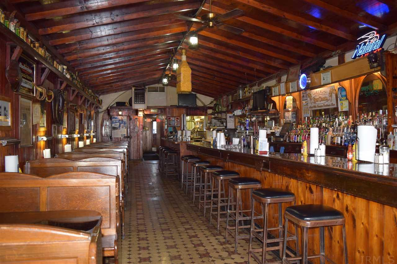Own a well established landmark bar/restaurant Business!  This building is huge and includes four addresses.  It can accommodate 150 people with a bar, family room and banquet room.  There is a three way liquor license as well as a tobacco and pull tab license.  All equipment as well as memorabilia stay with the property.  Upstairs features 7 apartments.  Income is $2400 to $2500 a monthly.  Above the bar area  is an owners living space/office in addition to the apartments.  This space has original woodwork.  This business has access to the city parking lot behind the bar. There are sidewalk areas as well to install outside dining.  You get all of this and so much more.  Come see your new business today!