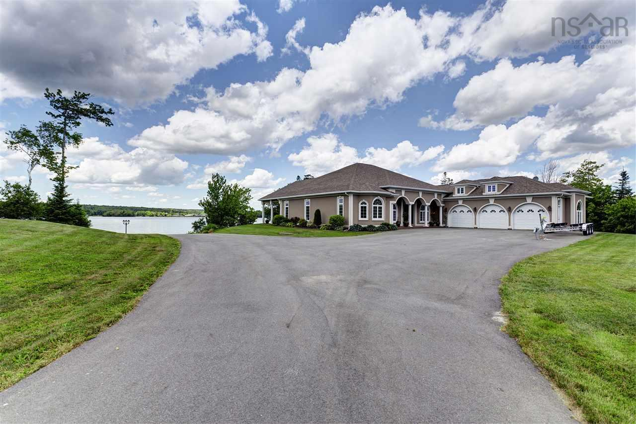 This amazing custom built lakefront home with an attached triple bay garage sits perfectly with a southwest exposure on it's very own peninsula, with over 1000+/- of water frontage in Sandy Point Estates on Porter's Lake, one of N.S. Premier lakes with access to the ocean. The home ,with lake views from almost every room, has many high-end features such as hardwood flooring, and slate tile throughout with custom trim and moldings to compliment stylish decor. The chef in the family will love the cherry wood kitchen, granite counters, built in appliances plus an island overlooking the Great Room with it's airtight wood burning fireplace. Multi-zoned in floor radiant heat gives comfort everywhere you step.This home has a wonderful split floor plan with the spacious Master Bdrm on one side with great water views and a stunning 5pc.marble ensuite. 2 other bedrooms are private on the other side of the home with their own full bath. Other bonus features are the home gym and games room with it's own wet bar. The home is wired for sound inside and outside where there is also a huge outdoor stamped concrete patio with a Hot Tub to relax and enjoy the magnificent sunsets over the lake year round if you choose. This property is a Boater's Paradise with over 1000 ft of water frontage and the dock and wharf facilities are included.