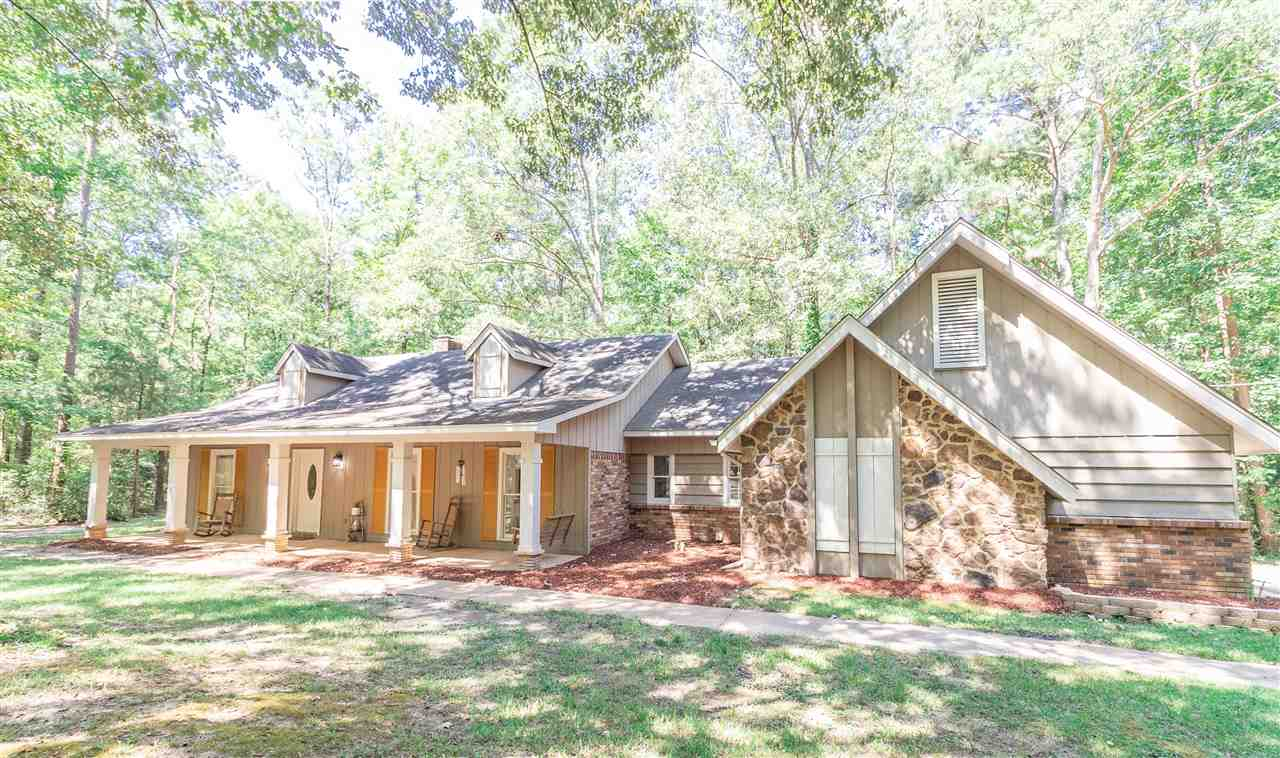Take a Look at this Amazing Property on 2+ acres nestled between Hardwoods and Pines. This Split Plan Home with it's distinct design offers 3 bedrooms and 2 full baths. The inviting front porch with swing will captivate you as you walk up to the front door entry. The home offers original wood floors in the Foyer, Great Room and Dining Room areas. Natural Light blossoms throughout this lovely home and the coziness of the wood burning fireplace in the large Great Room with Beamed Ceiling says it all. Two bedrooms are located just off the great room and share a hall bathroom accented with Shiplap wall panels. The Kitchen offers an abundance of storage with a wall pantry. A built-in desk area currently provides a Coffee Bar Station. The laundry room and access to the 2 car garage is just beyond. A quaint office nook separates the Private Master Suite from the Master Bath with double sink vanity and walk-in closet. An extra storage closet completes the Private Suite. Step out to the Covered Patio and take in the Beautiful View. Peaceful Sounds and Tranquil Living exemplify nature at it's best surrounding this remarkable home. Contact your Realtor today to schedule a tour!