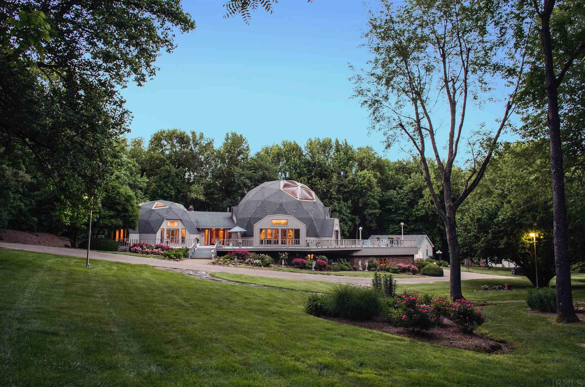 Evansville's preeminent geodesic dome house is on the market, and it's time to see it in a new light. Designed in 1981 by local husband and wife team Dr. Sandy Schen and restauranteur Jackie Schen, no other home offers the perfection of early 1980s/1990s high-end contemporary design, immense scale, and an oasis of landscaped acreage on Newburgh Road. With two domes, one soaring to nearly 28 feet on the interior, the roots of Buckminster Fuller are twice as prevalent here. Featuring over 12,000 square feet of living space, the home's major goal is prevalent throughout: to entertain family and friends, both near and far. The home's main level includes three formal dining areas, flooded with natural light, bringing the outside in. Two master suites, an executive library, and a living area in the smaller dome large enough for dining, sitting, and a concert grand piano. Domed ceilings show the signature transition from hexagons above to pentagons below. Custom art made for the home graces the soaring stairwell, while the open kitchen with commercial grade appliances anchors the heart of the home. The original master suite sits just off the kitchen and cork-floored dining area and works perfectly for private guest quarters. Featuring a vibrant accent wall of hand-painted French wall-paper, the home's original thrust of contemporary design is clear here - from clean contrasting tile floor, white track lighting, and en suite with Corian shower and soaker tub. The curved kitchen opens into the enormous 1990s addition, which includes a second open access to the finished basement, a vast entertaining and living area, and a Las Vegas worthy master suite boasting his and hers walk-in closets, copious amounts of Corian in the tub surround and walk in shower, and a walk-out to the inn-worthy rear covered deck. The home's three other bedrooms lie in the larger of the two domes, each with their own loft spaces, two connected by a Jack-and-Jill bathroom. Below grade, in the expansive walkout basement, sits a billiards area, executive office, 4th dining area, entertainment space with wet bar and dry bar, guest suite, music/theater room, and wine room. Outside, the original pool house welcomes you into a focal point of entertaining and hospitality with kitchen, guest suite, and open living area - all walking right out to the diving board, the home's sunset view to the west flanking the entire resort of architectural experience. Two domes. Two words. Geodesic deliciousness.
