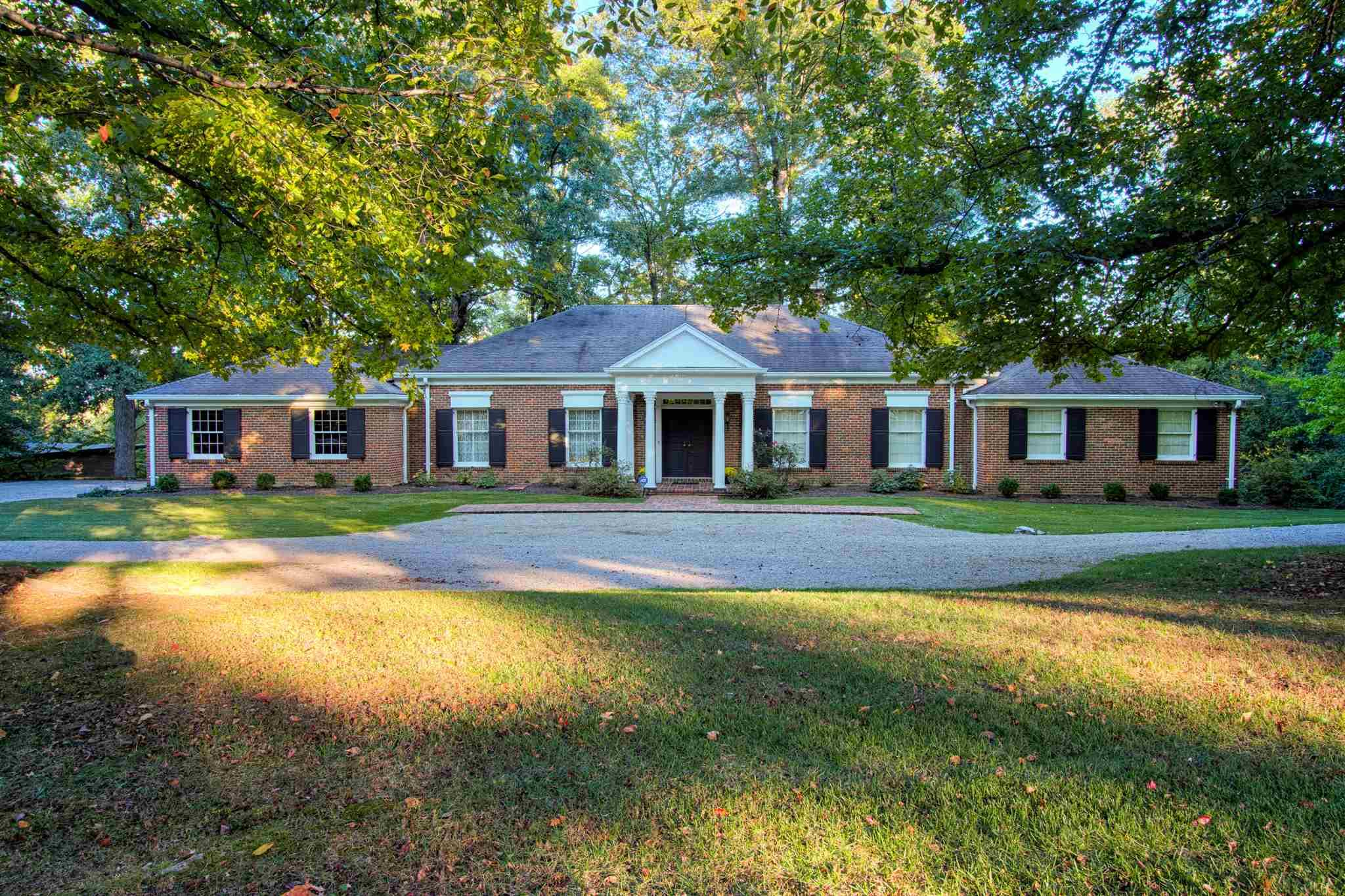 This McCutchanville Estate offers a private setting on 2.25+/- acres with lake frontage and beautiful views. This 4 bedroom, 3 bath home with walk-out lower level offers a new roof and has been loved and cared for by the same family over the years. The foyer with transom window opens to the spacious living room dining room combo making this floor plan perfect for entertaining. The large kitchen offers an abundance of cabinetry and is open to the dining area. The spacious great room with hardwood flooring has floor to ceiling windows providing beautiful views of the ground and lake. This great space offers an abundance of charm and character with beamed ceiling and a fireplace with wall of built-ins. The main level master bedroom offers double closets and a large master bath with walk-in shower. There are two additional main level bedrooms one with hardwood flooring and one with built-ins. There is also full hall bath with tub/shower combo. The large laundry located off the garage also has access to the back covered porch. The floored walk up attic space offers an abundance of space for storage and could be finished for additional living area if desired.  The finished walkout lower level offers a large family room with built-in wet bar, fireplace, and access to the large patio overlooking the grounds with mature trees and lake frontage. This level also offers an additional bedroom that is perfect for in-laws and guests with private access to a full hall bath with walk-in shower. The lower level offers an abundance of storage space including a workshop. This custom built one owner home is conveniently located with easy access to great schools, shopping, dining, and major employers.