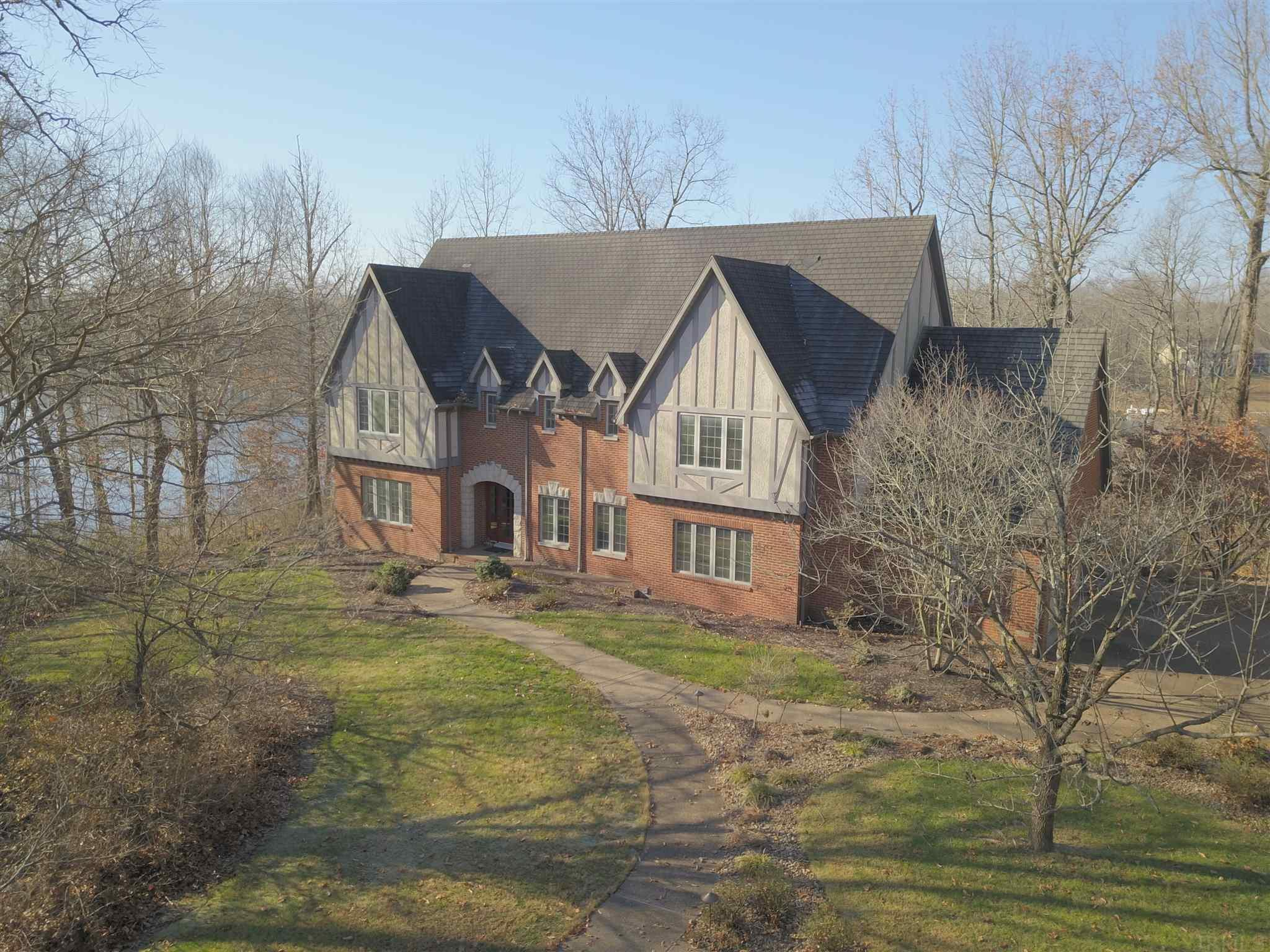 Rare find!  Wonderful Northside Estate on beautiful Kahre Lake.  This elegant Tudor home is in a Park-like setting on nearly 5 Wooded, Lakefront acres. Stunning views of 28 acre Kahre Lake from almost every room.  This spacious 6,126  square foot home with 5 bedrooms, 3.5 baths has so much to offer including a full Walk-Out Basement, an attached 2.5 Car Garage and a detached 2.5 Car Garage that includes a walk-up area for additional storage. The grand 2 story entry opens into a Formal Dining Room and a Formal Living Room. The main level Family Room boasts a Fireplace, built-in cabinetry and an abundance of windows.  The gourmet Eat-in Kitchen features Amish Cabinets, double ovens, warming drawer, wine refrigerator, 2 pantries and more.  It opens out to both a Screened Porch and a Patio with stunning lake views.  The Master Bedroom offers 2 large Walk-in Closets, a whirlpool tub, and a separate shower.  New Carpet throughout, 9 foot ceilings, generous Storage, 3 Fireplaces and so many impressive amenities.  The full Walk-out Basement includes a large Family Room with a Bar and Fireplace, A Pool/Game room, Office/Storage room, Workout or Workshop room, Bedroom, a Full Bath and lots of Windows.  This home offers you a retreat from the outside world while still being close to shopping and schools.