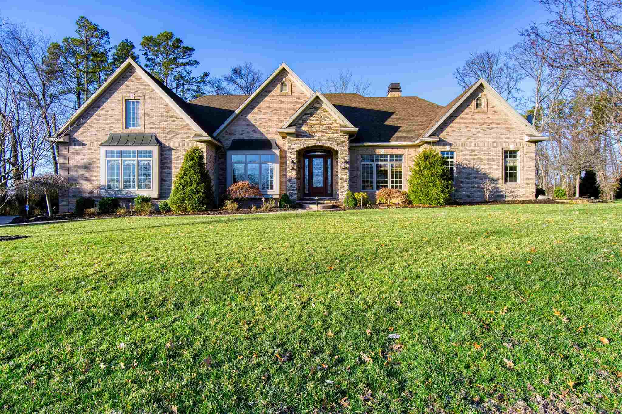 """Welcome to this exquisite custom-built brick ranch home peacefully situated on 2.5 acres on a private cul-de-sac. This immaculate home has been exceptionally maintained and shows like new construction.  Upon arrival you will fall in love with the setting, the stone and stamped concrete driveway, and the meticulously kept lawn and landscaping. Great curb appeal is just the beginning! As you enter the home, you will be impressed by 14' ceilings, an open floor plan, and an abundance of natural light. Quality construction is evident as you see the beautiful arched entry to the sitting room/office, 14' columns defining the dining room, 9.5"""" baseboards, and triple crown molding. Both the sitting room and dining room offer elegant lit tray ceilings and large windows. Continuing on you will be in awe of the expansive great room and kitchen with coffered ceilings,  wood burning stone fireplace with gas starter, built in bookcases, and an entire wall of windows that make the living space comfortable and cozy!  The gourmet kitchen starts with plenty of quality cabinetry, granite counter tops, stainless steel appliances; 6 burner gas cook top, double ovens, a warming drawer, dishwasher, microwave, ice maker, wine refrigerator, and trash compactor. Extras include a pot filler, roll out cabinet shelves, pantry, island with a prep sink/disposal, wet bar with its own sink, and the double kitchen sink/disposal. The kitchen offers plenty of counter space, bar top seating, planning desk, and breakfast nook and is open to the living area, making it the perfect place for entertaining. Outside, just off the kitchen, you'll find a screened in porch and large deck that overlook the wooded lot offering plenty of space for relaxation. The tv and the hot tub are included in sale. Rounding out this impressive home are 3 bedrooms (possibly 4) each with their own full bath, a huge bonus room that could easily be converted into a bedroom and bonus room, a laundry room, 2 half baths, and a master """