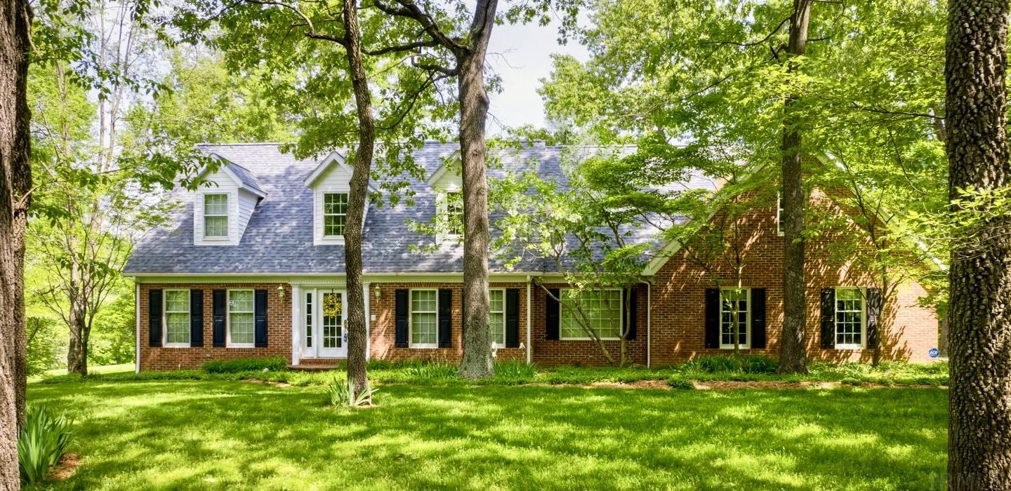 """Remarkable lakefront 4-bedroom, 5-bath home with 6 acres tucked away up a tree-lined concrete drive.  The aggregate circle drive and winding brick sidewalk guide you to the front door and two-story foyer.  This 5,300 sq. ft. home combines flawless craftsmanship with modern amenities.  The family room and master suite both have access through French Doors to the back patio overlooking the lake.  All bedrooms feature large walk-in closets and an """"at home"""" coziness that you will certainly appreciate. Exquisite details can be found throughout, such as crown mouldings, new hardwood flooring, Sub-Zero commercial-grade refrigerator, crisp white Corian countertops, 39x12 bonus room (could be 2 more bedrooms) plus upper level loft area, 12 station irrigation system w/ lake pump, abundance of storage, detached 3-car garage with finished bonus room, 3-zone geothermal heating and air system, security system, and much more.   The lower-level of the home offers an over-sized rec area, custom built-in entertainment center with a new TV, kitchenette, storage area with wooden shelving, and a half bath.   Outside you will fall in love with the breathtaking lake views, curved and multi-level patio.  In addition to the 6 car garage space there is a 24x40 insulated metal building with concrete floor, water and electric, the perfect place to store equipment.  New Roof in April 2019, manufacturers warranty still available on Geothermal system.  An incredible level of quality and finish, design and details resonate throughout this well maintained residence!"""