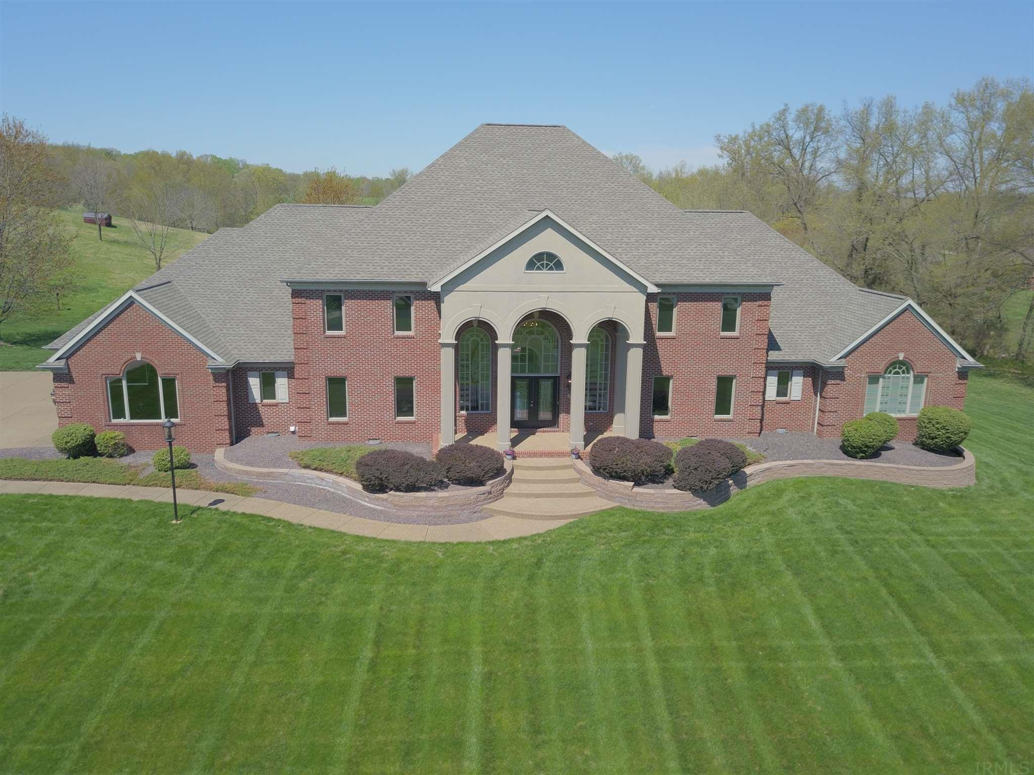 Now is your chance to own this Spectacular Estate! Located on a breathtaking 5.8 Acres in McCutchanville this One Owner has so much to offer. From the moment you arrive the long drive takes you past the beautifully manicured front lawn. The massive 2 story triple arched columned entry opens to the marble Foyer with grand curving twin staircase! Pass through an arched doorway to the Great room, also 2 story in height with coffered ceilings and beautiful wood stained built-ins flanking the Fireplace and another set of triple arched windows. The heart of the home is the Chef pleasing Kitchen with stainless appliances, SubZero refrigerator, granite tops, planning desk, over sized pantry, breakfast bar, center island and casual dining area with beautiful views of the back acreage, salt water pool and deck. Also on main level is a Formal dining room, Guest suite, Study and Owners Suite which includes the bedroom, sitting room, his and hers walk-in closets and a private bath!  Upstairs there are 2 sets of huge bedrooms each with a Jack and Jill bath separating. One features a bonus room all with loads of closet space! The walk out lower level boasts an inviting wet bar, rec area, Exercise room, full bath with changing room off of screened porch that leads out to the Pool. Other features include a 4 car garage, Security system, Irrigation system, Generator, One year home warranty, New roof 2018, new HVAC units 2015, all new floor covering and most entry doors, plumbing,  light fixtures and appliances recently replaced. Pool liner and pump '16, auto cover '17. Hurry, Immediate Possession!