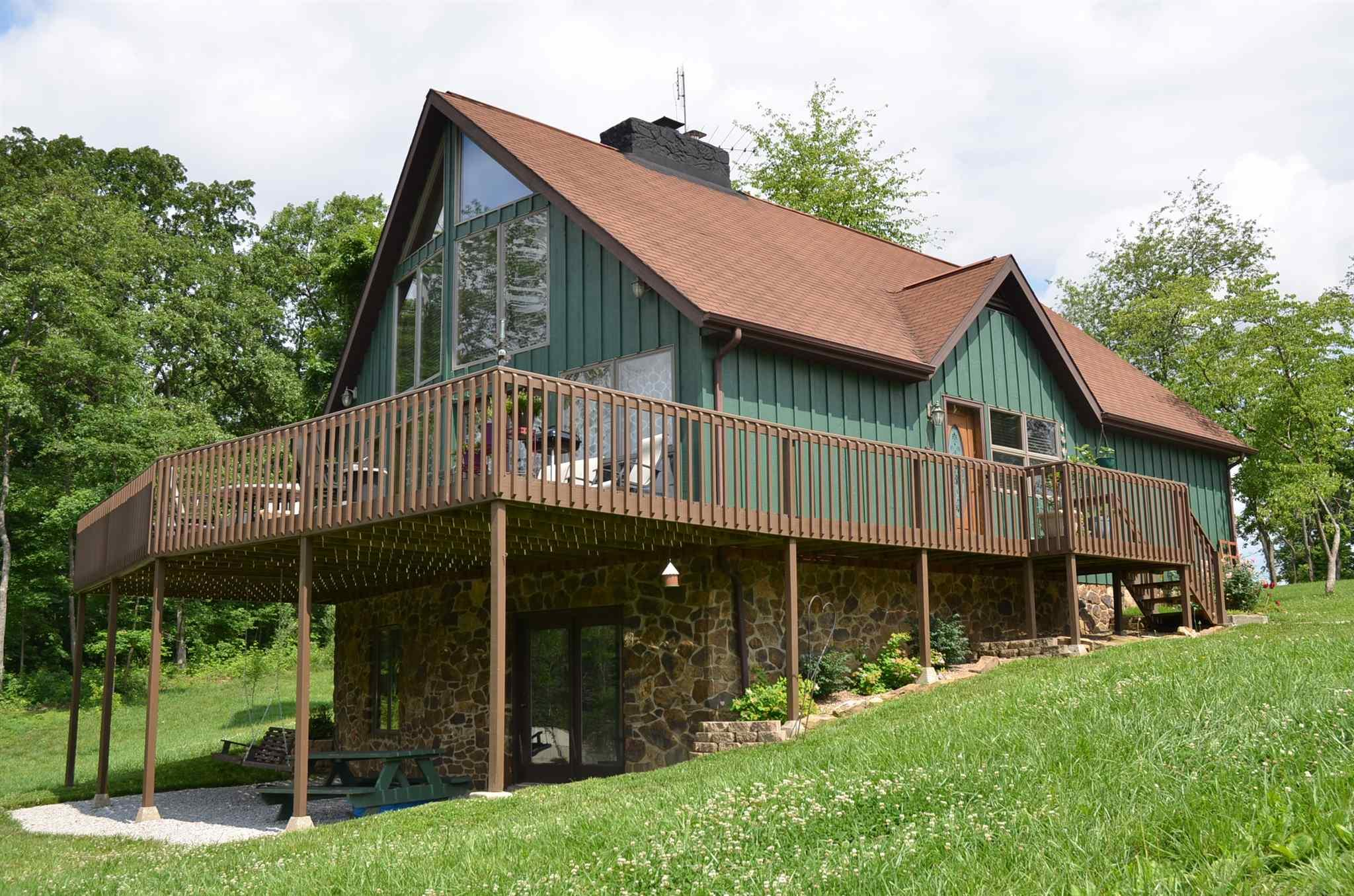 PICTURESQUE & PRIVATE...a world of privacy can be yours!  This three bedroom two bath home is tucked away on over five acres of pastoral splendor at the end of a quiet no-through lane. Amenities include a cheerful country kitchen with ample cabinetry which is open to the dining and living room areas centered with a fieldstone floor-to-ceiling fireplace, a magnificent window wall that appears to bring the great outdoors in, a large family-sized deck for a bird's eye view of your own private lake, a full finished walk-out basement, and an over-sized two-car detached garage...this is a rare offering that is at peace with nature so reward yourself with the home you deserve!