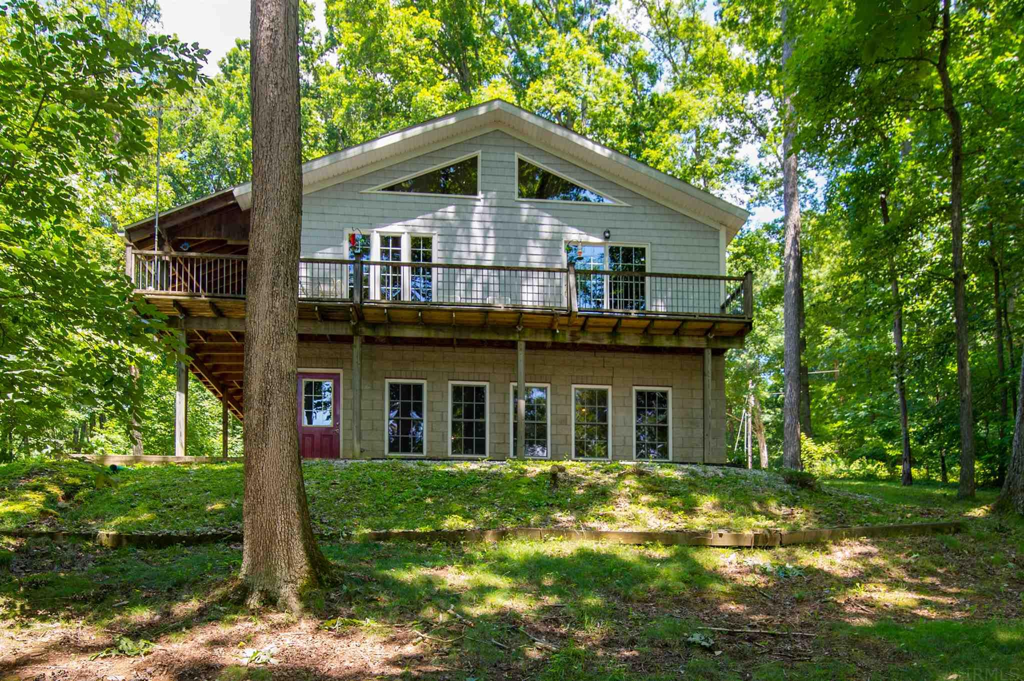 "This unique 2400 sq. ft. Post and Beam or Timber Frame home is nestled in the woods by 65 acre Lake Helmerich.  The exposed beams inside the 3 bedroom 2 bath give a feeling of quality construction.  Home is super insulated with walls and roof covered in 4'X 8' sheet panels with 4 "" of Styrofoam sandwiched inside. The open concept construction helps to highlight the large oak beamed interior with the cathedral ceilings. Exterior walls are vinyl shakes.  The hardwood floors are all solid teak and doors are custom solid oak. Kitchen counters are solid granite and all appliances are included except the gas range which will be replaced with a new range and the washer and dryer and the upright freezer .Check out the huge island in the kitchen and the custom cabinetry.     Windows give splendid views out into the woods and to the lake with your own boat dock and pontoon boat ready to launch. The wood stove on the main level serves as a secondary heat source if so desired. The S and W sides of the home have 76 feet of porches with over half covered.  White tail deer and wild turkey can often be observed as they make their way to the lake for a cool drink. Fishing has been good.  The 18 X 24 shed is added to the back of the 3 car garage. The attached shop and garage  have heat and AC.  The gated community provides good security. Your village has 160 acres of recreational water in 8 lakes for your enjoyment and 3 swimming pools. In spring time the village is ablaze with blooming red bud and dogwood trees and then fall gives us blazing maple tree foliage.  Get close to nature and make this your own nature sanctuary."