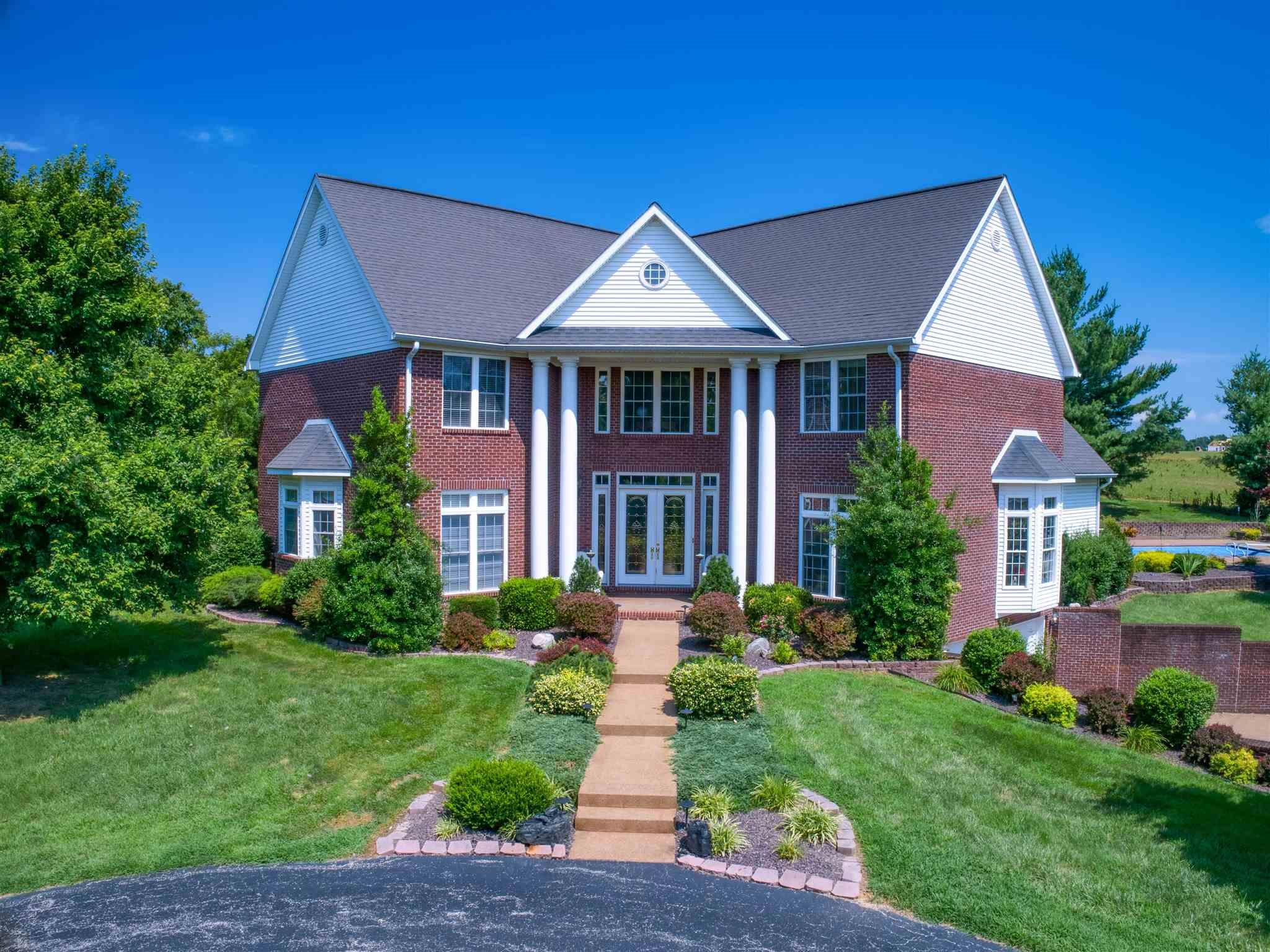 One of kind Luxury Plantation style Estate with private security gate on 9+ acres situated on the desirable west side of Evansville! This 2-story brick home is nestled high on a hill at the end of a beautiful tree-lined circle driveway. Featuring 5 bedrooms, 3 full baths, and 2 half baths. The 2 story columned entry features and a large open staircase. Foyer leads to a grand 25 x 44 two-story great room with lots of open space perfect for a game room/entertainment area. Nice theater room with leather seating and access to a half bath that also serves as the pool bathroom. Wood and tile surround the wood burning fireplace with a gas starter in the living room. The living room opens up to the eat-in kitchen which offers granite counter tops, a bar, a built-in wine rack, and stainless sink. Off the kitchen is the dining room. Lots of storage in the laundry/utility room with over and under counter cabinets, plentiful counter space, and a closet. The first floor master bedroom offers a Jacuzzi tub, with tile surround. The master bath has a double vanity, marble flooring, stand up 3-headed tile shower, and plenty of closet space. Upstairs are four large bedrooms, two bedrooms on each side of the open staircase. Both sets of rooms have a Jack and Jill bath between them. Back off the kitchen is a staircase leading to the basement with a room for more storage. Large oversized garage under the home could accommodated up to four cars. There are several additional basement storage rooms. On the grounds is a 48x64 detached garage with long built-in workbenches and is heated and cooled. Stairs lead up to an above garage apartment making this home great for multi-generation families and guests. The apartment has a full bath and is setup to add a kitchen if needed. Behind the home is the in-ground, heated pool with a diving board, and automatic cover. Not far is a heated and cooled playhouse. Seller states that he owns half of the lake at the left of the property when entering the gate. Don't miss seeing this one of a kind property!  Seller understands that the Buyer will want to do some redecorating, so seller is offering a $50,000 redecorating allowance.