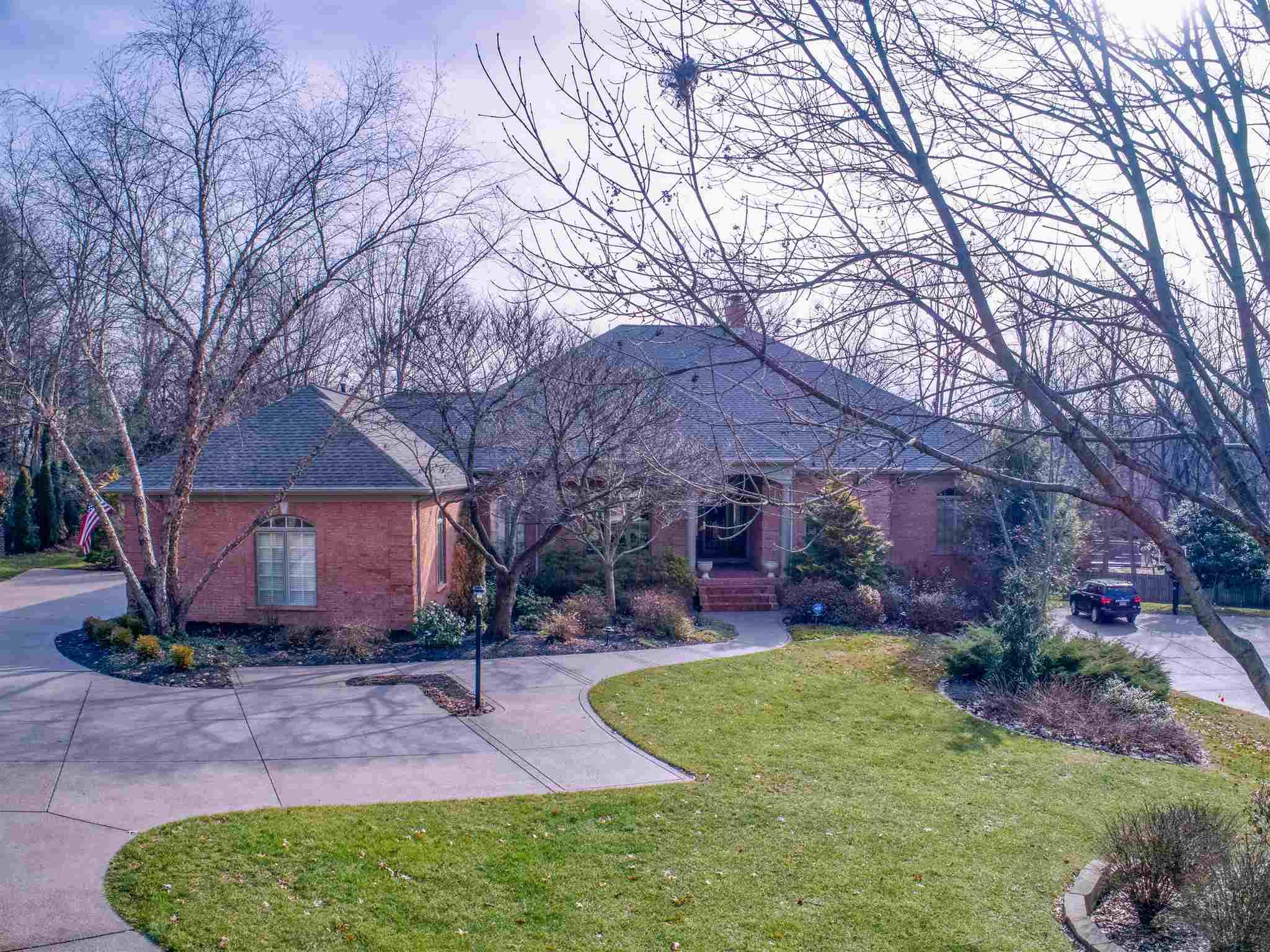 This custom built home is truly one of a kind. The sprawling ranch located in The Oaks Subdivision is deceptive in size. From the road you can never imagine what is inside. Extensive landscaping welcomes you as you arrive. Hardwood floors flow from the foyer to the dining room. The formal living room with 20' vaulted ceiling overlooks a two story indoor atrium with natural light galore and the backyard. The kitchen will definitely please the cook of the household. An abundance of cabinets and counter space including walk-in pantry, planning desk, raised breakfast bar and large island are just a few of the amenities you will find. The hearth room off the kitchen is where you will enjoy chilly evenings around the fireplace. The laundry room provides ample space with a utility sink and another planning desk. The master bedroom suite area is generous in size with an adjoining study including a duel sided gas fireplace, rich wood bookcases, and cabinets. An attached master bath has double vanities, large tub and separate shower. The walk-in closet has custom built-in shelves and drawers. Two additional bedrooms with a shared full bath, 2 half baths, a meditation area and cubby lockers complete the main floor. The lower level provides a wonderful family room with fireplace and built-in bookcases. Three more bedrooms, one full bath and another half bath along with a kitchenette, craft area, pool table or exercise room and a huge unfinished storage room finish off this level.  Outside you will find the most relaxing covered porch ever. The private, park like backyard has blooming red bud trees in the spring, with 18 species of trees on the property. The heated pool has an automatic cover and diving board. Total of 6 bedrooms, 3 full baths, 3 half baths, 3 car garage, and a safe room.  Extra features include walk up attic storage, ADT security system, whole house wired for sound system, and  backup generator.