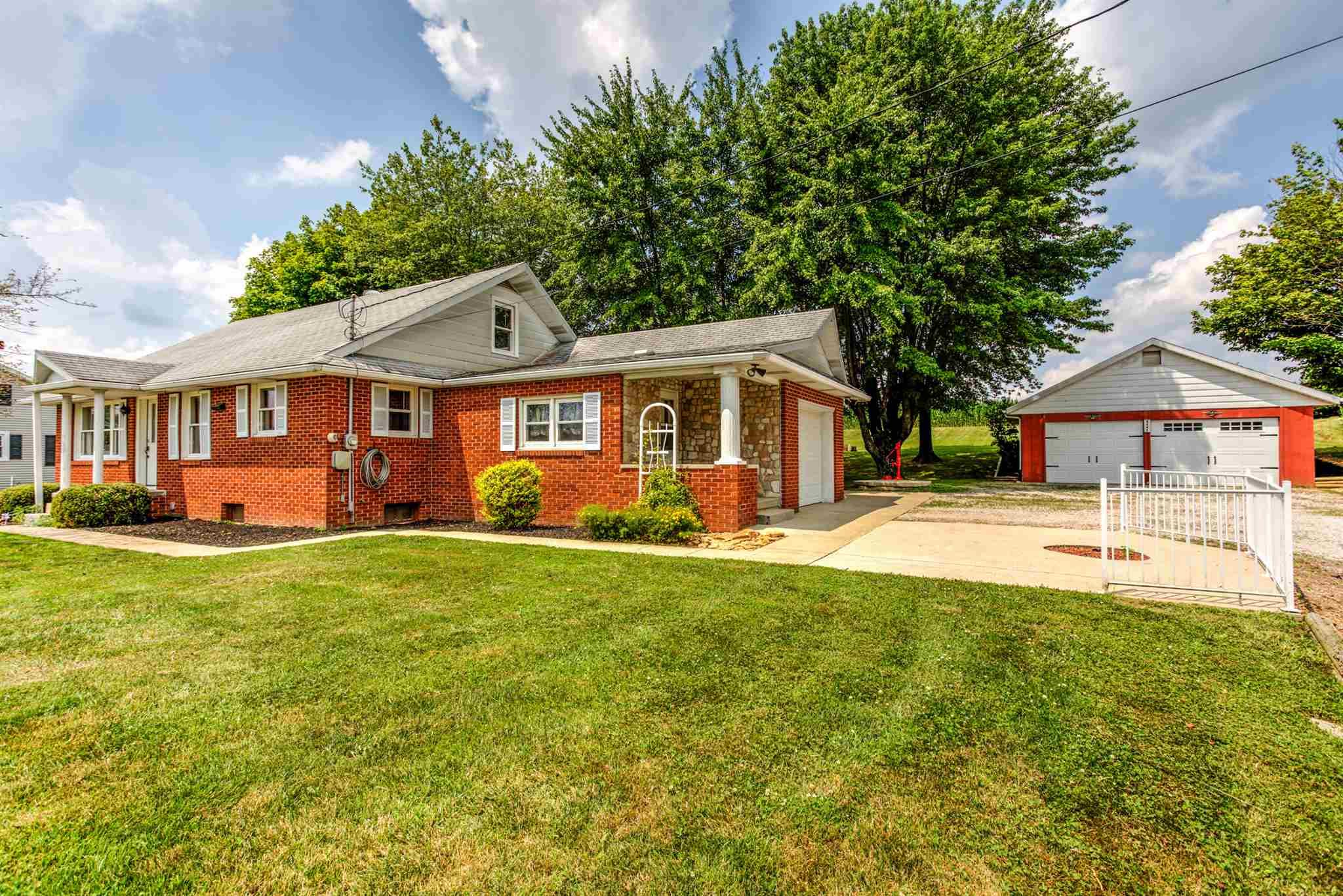 All brick home in a rural setting in SE Dubois School District.  This home features 3 bedrooms, 1.5 bathrooms, and a open floor plan with family/dining/kitchen area.  The kitchen has all appliances included.  Nice large laundry room with extra storage as well.  Two of the bedrooms are on the main floor with a full bathroom.  The upstairs is a large bedroom area with a half bathroom.  The main floor is original wood floors.  The house has a unfinished basement for extra space or storage.  The outside is wonderful with a attached 1 car garage and a detached 2 car garage.  There is an additional shed for extra storage as well.  Enjoy the evenings looking out at the countryside on this beautiful lot.  Additional info:  Blown insulation in attic and tankless water heater.