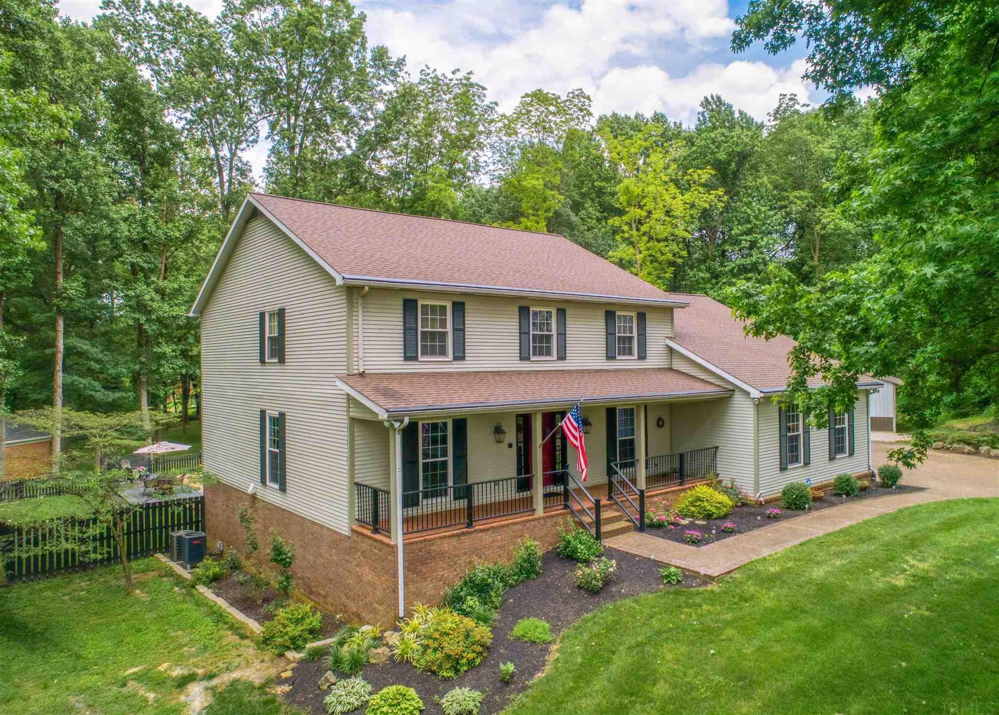 A long circle driveway leads up to this unique modern colonial inspired two story. The front door opens up to a large brick floored foyer with hall closet and staircase.  A Formal living room is off to the left with attached dining room that has crown molding and hardwood floors that flow through both into the kitchen.  Wood beams draw your eye upwards to the ceiling as you enter the kitchen. The kitchen is outfitted with rustic features such as brick accent wall with built-in counter top, black cabinets, large island with cook top, double ovens, planning desk and granite counter tops.  there is also space for a table with a view of the pool area outside.  Off of the kitchen is a family room with wood burning fireplace, built-in shelves and French doors leading out to the screened in porch overlooking the tranquil backyard.  The main floor laundry is huge with 2 walls of cabinets, granite counter tops, wash sink and walk-in pantry.  Upstairs the master bed room has new hardwood  flooring, crown molding and an updated master bath with walk in closet.  There are 3 more bedrooms on the upper level as well as an office or bonus  and a shared full bath.  The finished walk-out basement is spacious and open with a remolded full bath, kitchenette with new cabinets, sink and storage area.  The basement offers a built-in Sauna for your relaxation and enjoyment.  Outside is an in-ground pool with diving board, sun deck and upper deck that leads back into the screened in porch.  Finishing off this home is the  24 x 24 detached garage for additional parking or workshop.