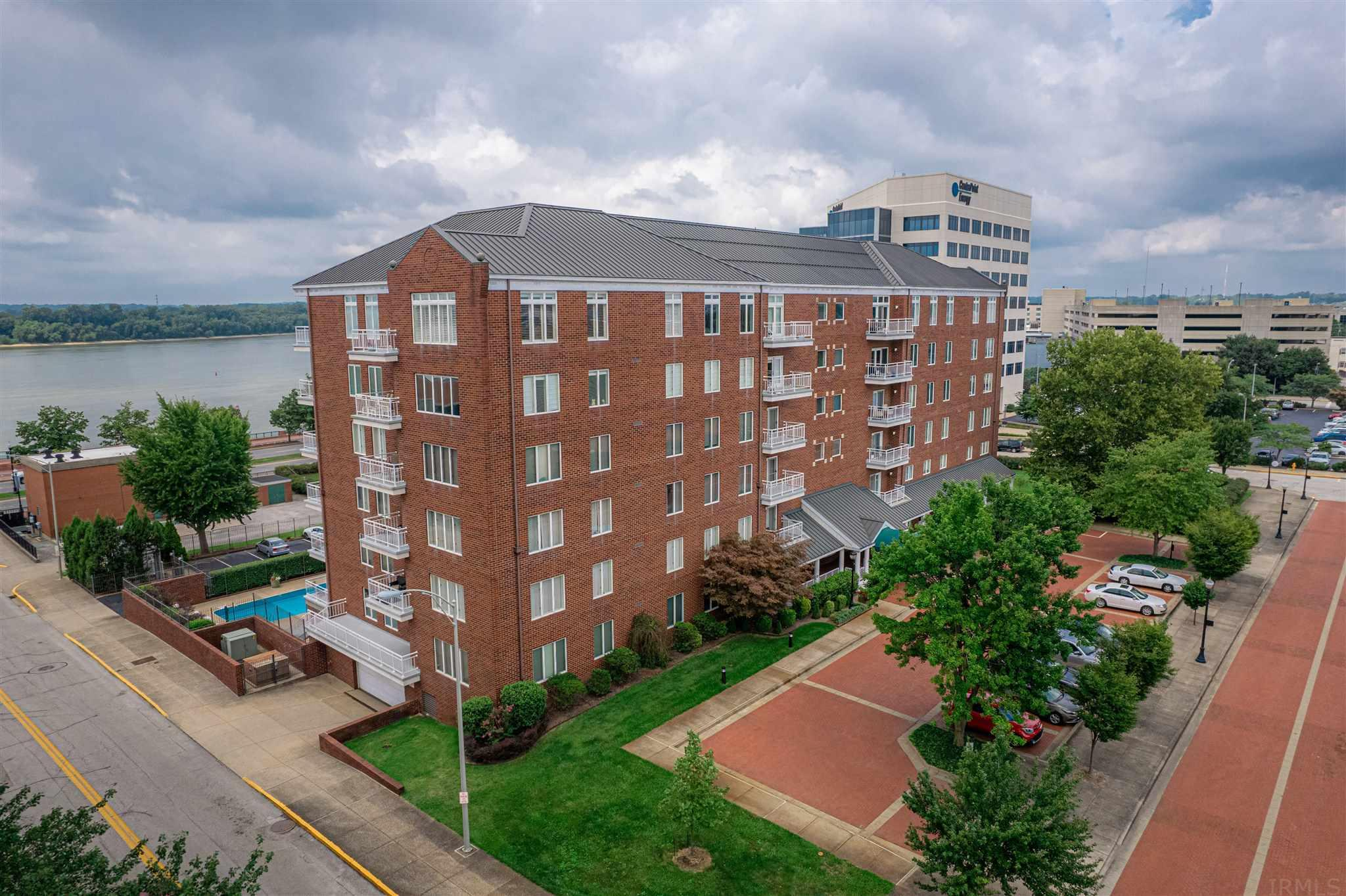 The real estate consists of one of the largest units in the Riverfront Condominium complex: a wonderful 1,930 sq. ft., 2 bedroom, 2 bath home conveniently located on the first floor.  The marble tile entry opens into a bright, spacious living / dining area with hardwood flooring, crown molding, built-in entertainment cabinet & beautiful views of the Ohio River that can be enjoyed from inside or from outside on the lovely balcony.  Located off the dining area, the kitchen is equipped with double stainless steel sink, KitchenAid side by side refrigerator, Whirlpool dishwasher, electric cooktop, Frigidaire wall oven and built-in microwave.  Across the hall from the full guest bath, the second bedroom features built-in cabinetry, crown molding, chair rail, ceiling fan & access to the balcony overlooking the river.  The master bedroom suite boasts crown molding, built-in cabinetry, ceiling fan, two closets (one of which is a 8' x 7' walk-in) and full bath with twin sink vanity & shower.  Located off the foyer, the laundry room has a washer & dryer that will be included in the sale.  Riverfront Condominiums offer many wonderful amenities including security, a party room with kitchen, a beautiful pool with river views, a secure underground parking garage with a reserved parking spot for each unit, two storage areas (one on the unit floor & one in the parking garage) and a reserved space in the parking lot. The monthly association fee of $567 includes water, trash, basic Wow cable and covers commons area maintenance.