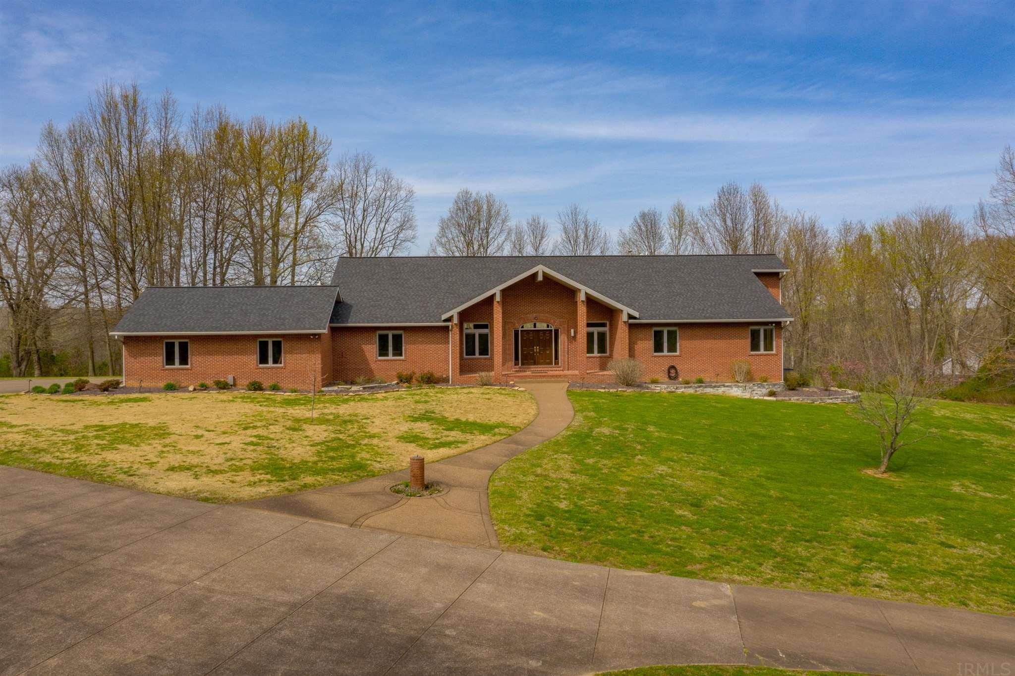 County Living at its best on over 19 acres. The inside of this beautiful home was  thoughtfully designed with entertaining in min.  Boasting an open spacious floorplan with vaulted ceilings throughout. This one owner custom built home is a must see.  The main floor features a formal dining room, great room with fireplace, an Owner's suite with whirlpool tub, spa, and separate shower. All have an amazing views of the property.  Additionally there are two bedrooms located on the first floor. The finished walkout lower level offers a large family room with a fireplace, kitchenette, game area, fourth bedroom and a full bath.  Outdoors you will enjoy the evenings watching wildlife from your very own screened porch or spacious deck. Lots of yard space and room to play or have animals. Detached over 4320 sq ft detached buildings (70x48 and 48x20) are combined to make one climate controlled garage. The garage has a workshop, lift, RV hook-ups and a 14' clearance perfect for any RV.  The garage could easily be converted to horse stalls if desired. This home is Located within minutes of shopping, schools and hospitals.