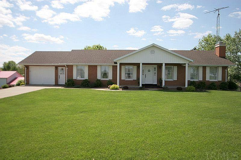Situated on a well manicured .80 acre lot is this all brick 1800 sq. ft. home.  Great location with a country feel but close to Jasper, Ferdinand, Huntingburg and the Interstate. This quality constructed home features 3-4 bedrooms, 2 full bathrooms, plastered walls throughout,  a full finished  walk-out basement, a large welcoming front porch  and multiple garages. The spacious kitchen and breakfast nook offers plenty of space for the cook in the family.  Located just off of the breakfast nook is a  brand new large raised deck.  A formal dining room is also located just off of the kitchen for convenience with a spacious living room adjacent through glass divided lite pocket doors. The oversized master bedroom is  a bonus allowing plenty of space for a king size bed. Two additional bedrooms and a twin sink bathroom complete level one. The lower level features a second full kitchen and dining/game area, a cozy family room with a pretty stone fireplace with a wood burning insert, an office/work-out room, a large bedroom, a full bathroom, and spacious laundry room. There is an upper garage, a lower garage, and a 22X30 detached garage. An attractive lower patio is located just through the walk-out doors of the lower level.  This home has been well cared for and is extremely neat and  clean inside and out. Updates include a 10 year old roof, 2019 water heater, and an  approximately 12-13 year old furnace and AC. Attractive well manicured landscaping surrounds the home.  The adjacent .76 acre Lot could be purchased  for a price of $29,900 but will not be sold alone before the home.