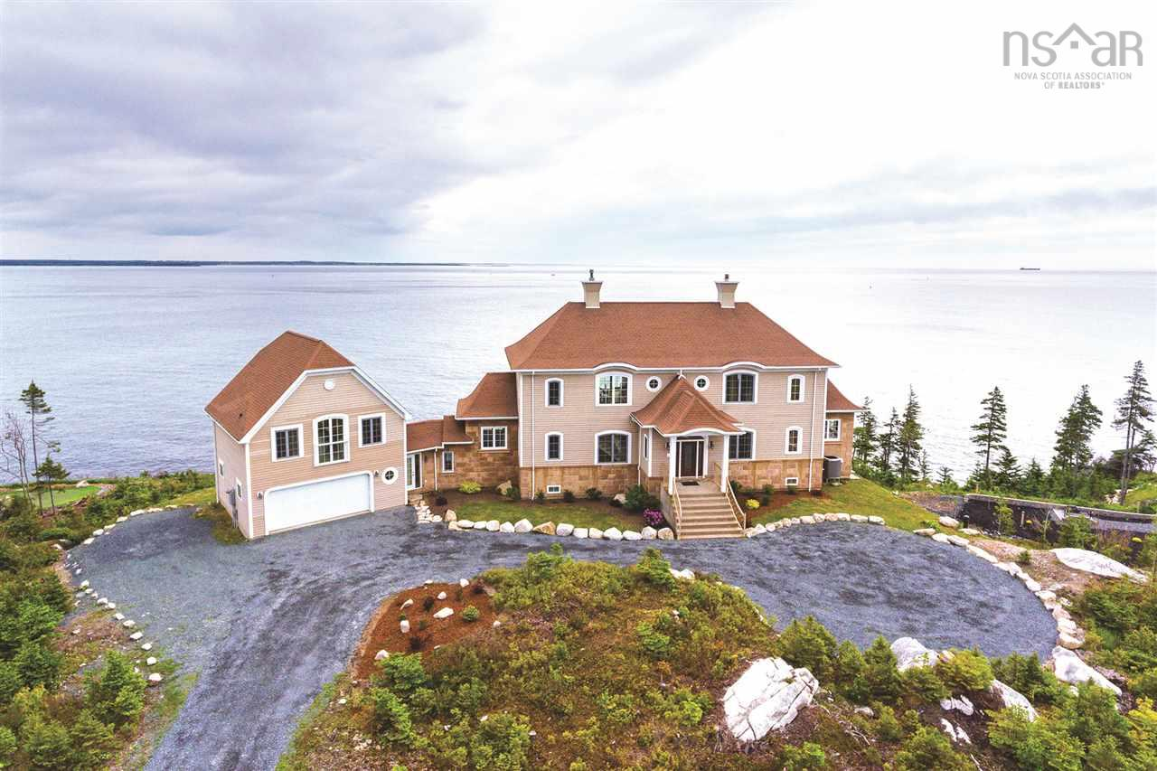 """A remarkable home the whole family will love nestled in the Oceanside community known as """"The Breakers"""" private and relaxing, but only 12 minutes from Halifax.  Located on a quiet court you will find this exceptional home that is built on a granite cliff to take full advantage of the panoramic ocean views including the mouth of the Halifax Harbour. This home has undergone a major retrofit from the outside in, to help withstand the elements. Inside, you are greeted with cathedral height ceilings, main floor custom kitchen with double islands, central to a large dining room, with patio doors to the deck where you can take in the captivating morning sunrises, listen to the waves crashing on the rocks and watch the ships sail by.  Upstairs, the master retreat offers ocean views, large walk-in closet, ensuite bathroom with soaker tub and an oversized custom titled shower.  One additional ocean view bedroom with ensuite and lovely reading area are located on the upper floor.  Lower level is fully finished and boasts a fantastic family room, two additional bedrooms with ensuite, perfect for guests. Lastly, enjoy the ocean view loft area above the garage complete with 3 pc bath.  All of this, coupled with beautiful gardens, and 200 feet of coastline you may never want to leave!"""