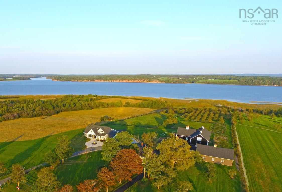 A picture of exquisite taste & style, this 60 acre grand estate with panoramic views of the Minas Basin has much to offer. Currently used as an equine facility, however the property lends itself to a wide variety of opportunities. This location is absolutely perfect for viticulture and the wine industry as you are in the heart of the highest concentrations of wineries and production in Atlantic Canada. The slope, soil, proximity to a body of water and average temperatures ticks all the boxes of prime winery material, the existing mature orchard is a bonus. Included are a 6700 sf main homestead and finished attached garage, a 3000 sf workshop, a 24x36 two level utility building and a Kentucky inspired 7800 sf stable. Just an easy 45 mins to the Airport and 30 minutes to the city. The possibilities for this property are endless!